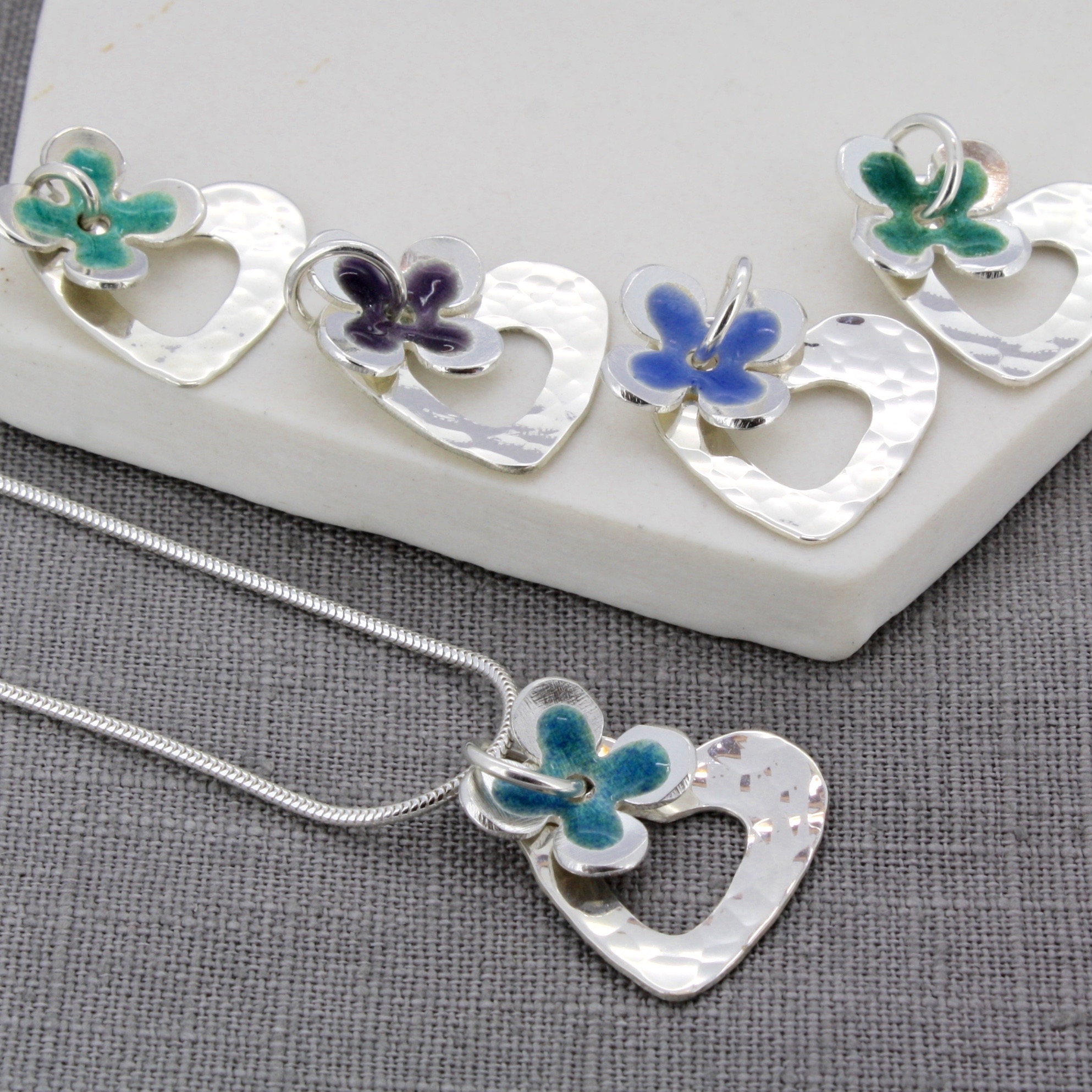 Personalised enamel daisy and hammered heart pendants